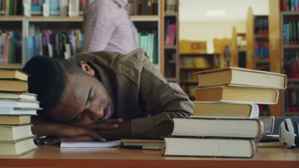 Africká americká hezký mladý muž student sedí u stolu velkými hromadami knih v knihovně. Jeho hlava je lhaní na stole spí a unavený.