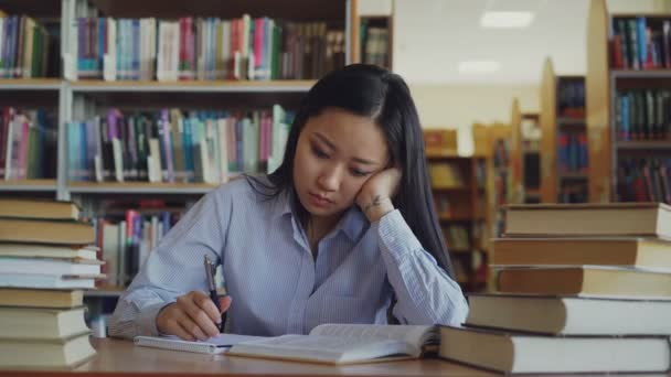 Young asian teenage girl is sitting at desk in big library rewriting text from book. She is tired and exhausted, looking through text closing book and turning away