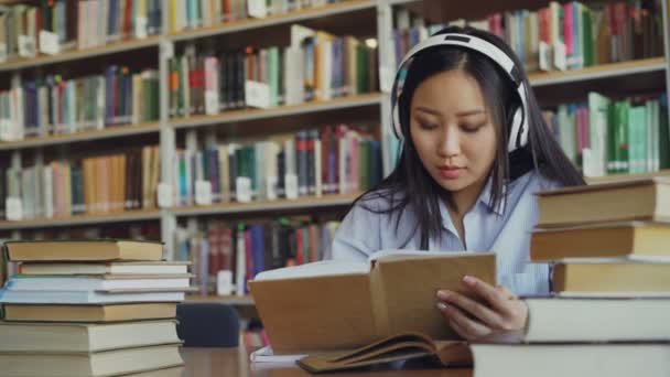 Pretty positive asian teenage student with headphones on head listening to music is sitting at table in big library holding book and writing down summary