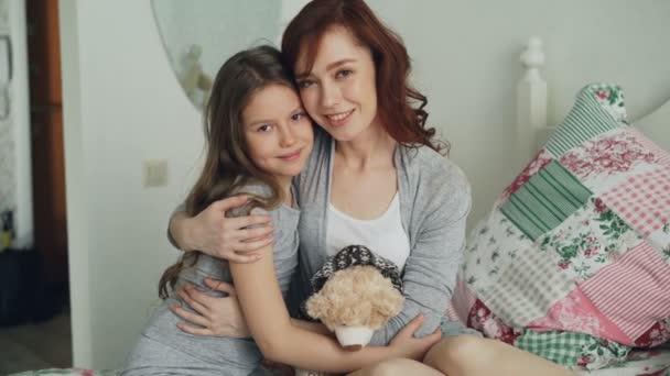 Porträt eines entzückenden lächelnden Mädchens, das seine glückliche Mutter umarmt und gemeinsam in die Kamera schaut, während es zu Hause im hellen Schlafzimmer auf dem Bett sitzt