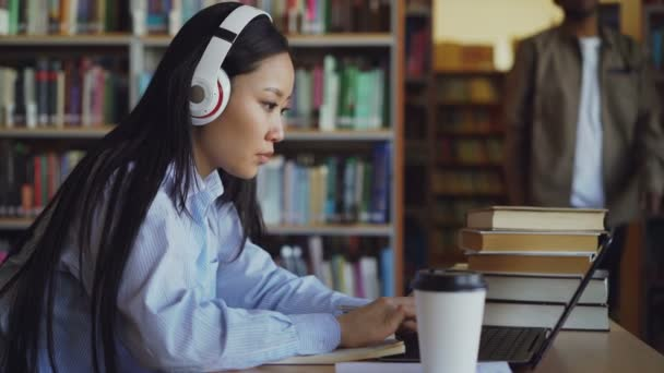 Beautiful asian female student in headphones sitting at desk in library working concentrated at school project. Young girl typing on laptop, drinking coffee and writing in copybook