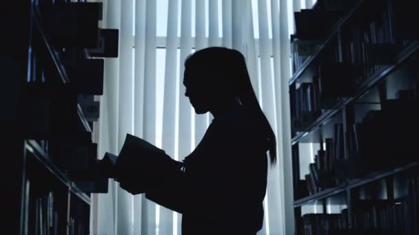 Silhouette of young student girl standing among bookshelves in big library against window holding book turning over pages and reading