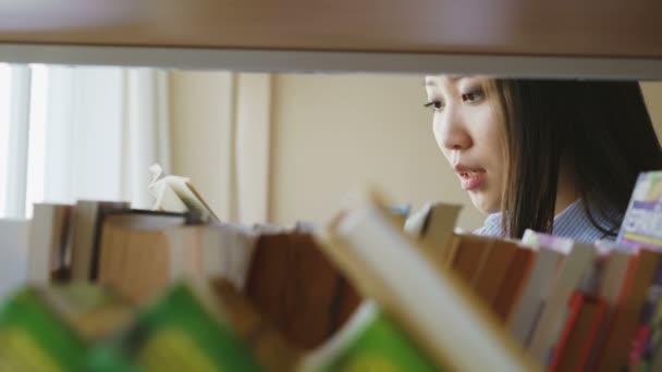 Portrét krásné asijské vážné ženské studenta stojící poblíž police s knihami ve velkých lighty knihovně drží učebnicový obracet stránky čtení