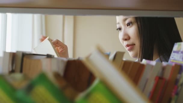 Attractive asian student girl standing near shelf with books in university library holding book turning over pages reading it