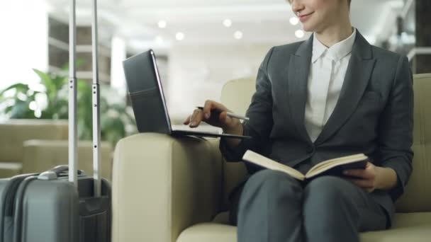 Tilt up of blonde businesswoman sitting in armchair in hotel lobby writing in notepad and using laptop computer. Business, travel and people concept