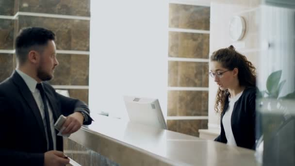 Businessman guest talking with receptionist girl standing at desk in hotel reception and paying bill with credit card via contactless payment technology . Business, travel and people concept
