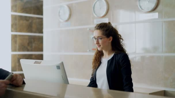 Receptionist girl at in hotel talking with arrived businessman about check-in and giving key card to man . Business, travel and people concept