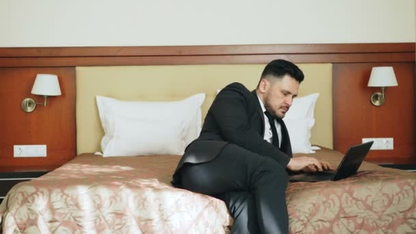 Pan shot of concentrated businessman in suit working on laptop while sitting on bed in hotel room. Business, travel and people concept