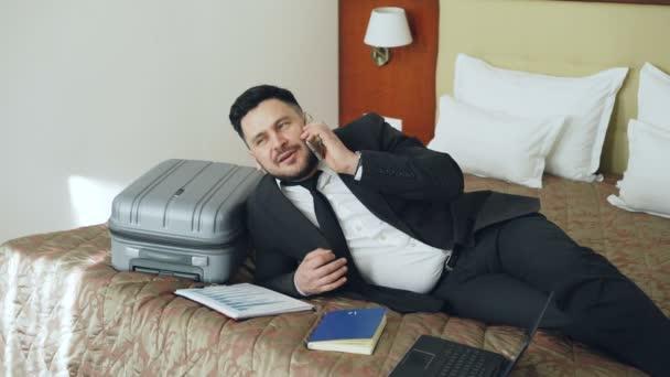 Veselá podnikatel mluví mobilní telefon když ležel na posteli v hotelovém pokoji. Cestování, podnikání a lidí koncepce