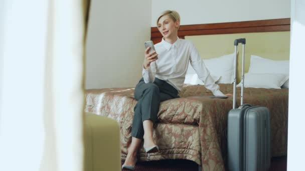 Happy businesswoman talking with family via online video chat using smrtphone camera sitting on bed in hotel room. Travel, business and people concept