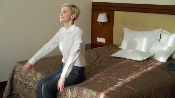 Usmíval se podnikatelka pádu a ležící na posteli uvolněné v hotelovém pokoji. Cestování, podnikání a lidí koncepce