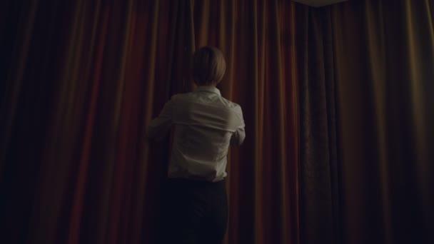 Geschäftsfrau enthüllen Vorhänge im Zimmer am Morgen und in Fenster suchen