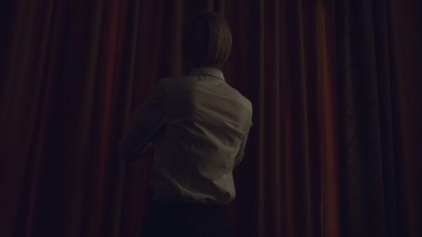 Zpomalený pohyb blond ženy prozradit záclony v hotelovém pokoji na ráno a při pohledu do okna