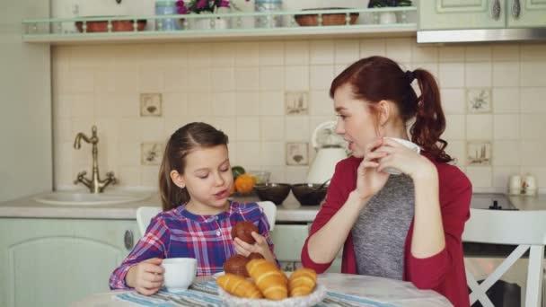 Boldog anya és aranyos lánya reggelizik Muffin evés és beszél otthon a modern konyha. Család, élelmiszer, home és emberek koncepció