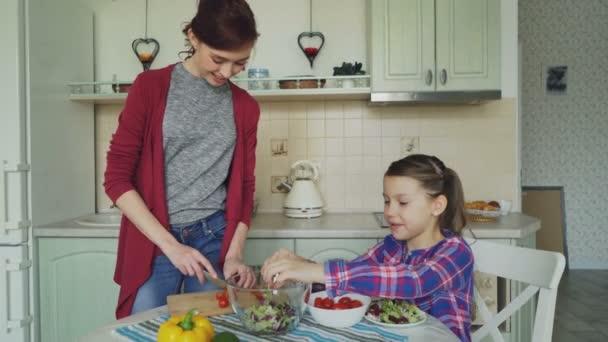 Šťastná Maminka a veselá dcera kuchaře salátu spolu v kuchyni doma řezání zeleniny a mluví. Rodina, vaření a lidé koncepce