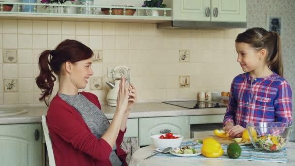 Mladá matka mluví foto na smartphone fotoaparát její roztomilé usměvavé dcery vaření krájení zeleniny v kuchyni doma. Rodina, cook a lidé koncepce