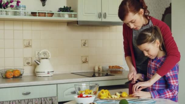 Young pretty mother teaching her cute daughter to cut vegetables properly. Little girl cooking together with loving mom at home in modern kithcen
