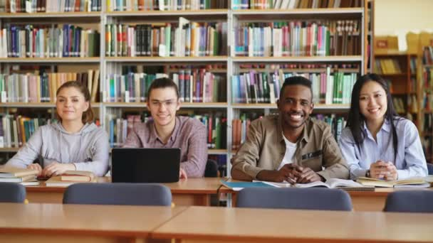 Portrait of four multi-ethnic students sitting at long desk in big spacious library with piles of books looking at camera and smiling positively