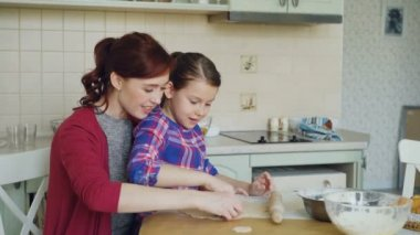 Smiling mother and cute daughter making cookies together using bakery forms while sitting in modern kitchen at home. Family, food and people concept