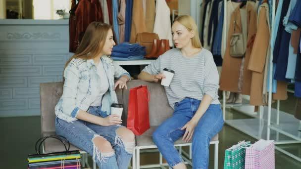 051d7a8bc57 Twee jonge vrouwen zitten op stoelen leer bedekte in kleding boetiek en  chatten na het winkelen. Mooie moderne womens slaan met veel kleding in  achtergrond– ...