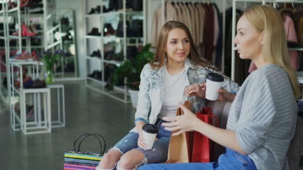 Dvě atraktivní dívky sedí a mluví v Dámské oblečením po nakupování. Stylové barevné oděvy, obuv a kabelky v pozadí