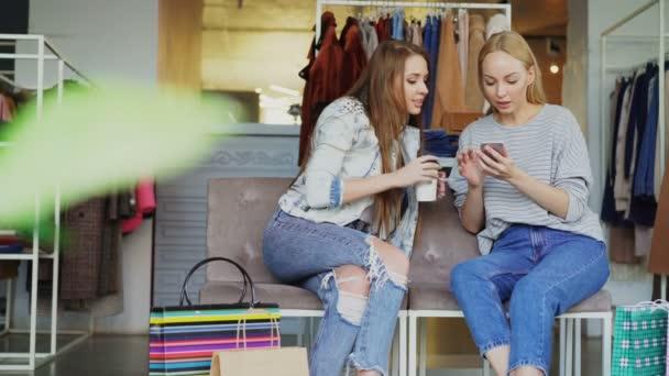 Kamarádky mluví a kontrola smartphone vsedě je obchodní centrum. Dámské oděvy a papírové pytle v pozadí