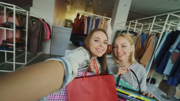 Point of view shot of two beautiful young women making selfie with paper bags in womens clothing department. Girls are posing, laughing and chatting happily