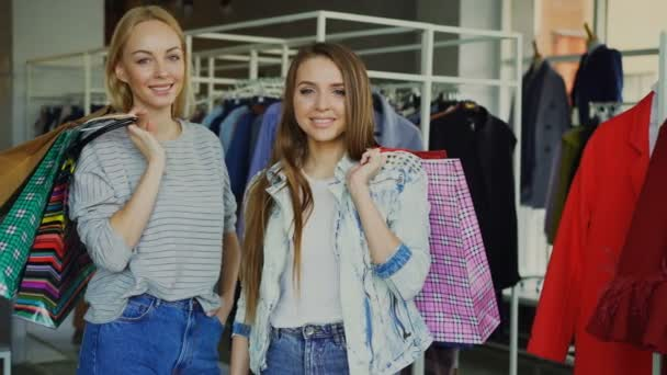 Portrait of beautiful young women are standing with paper bags in their hands in womens clothes boutique. Fashionable clothes, bags, shoes and baloons in background.
