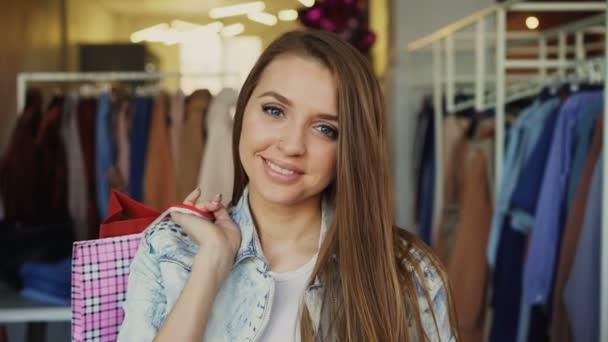 Detail portrét atraktivní mladá dívka stojící papírové tašky v obchodu s oblečením a při pohledu na fotoaparát s úsměvem. Stylové dámské oblečení je v pozadí