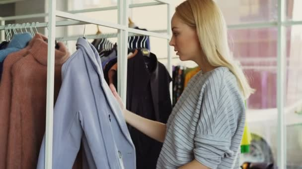 8f3f6afd475 Close-up shot of young woman choosing coat in shop. First she is examining  fabric , looking ...