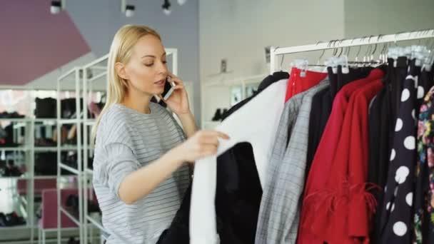 Zákaznici se pomalu prochází módní oblečení na závěs v prostorné prodejně. Ostatní zákazníci se pohybují s oblečení a boty na pozadí