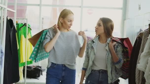 Dvě kamarádky se pomalu procházeli prostorné butikové. Oni se drží četné papírové sáčky, chatování a při pohledu na krásné oblečení a boty na věšáky a poličky