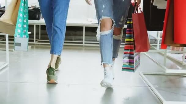 Alacsony Nézd lányok lábak séta lassan tágas boltjában. Hölgyeim viselt farmer és modern oktatók, és a könyv színes papír táskák.