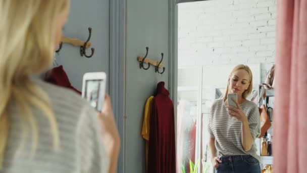 Pretty blond woman is making mirror selfie with smart phone while standing in fitting room in clothes boutique. She is posing, moving and smiling carelessly.