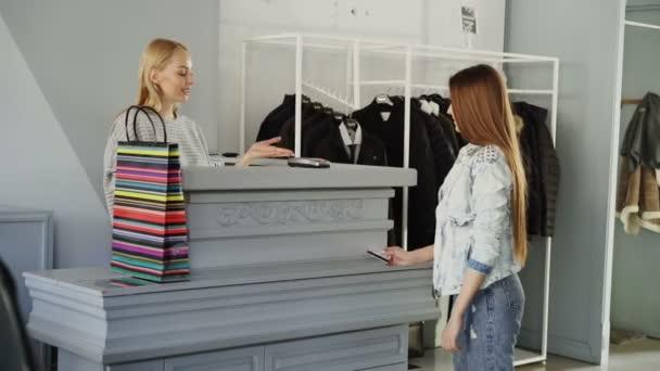 Veselá zákazník platí kreditní kartou zakoupené oblečení stoje u pokladní přepážky. Prodavač je přijetí transakce a dávat jí papírový sáček