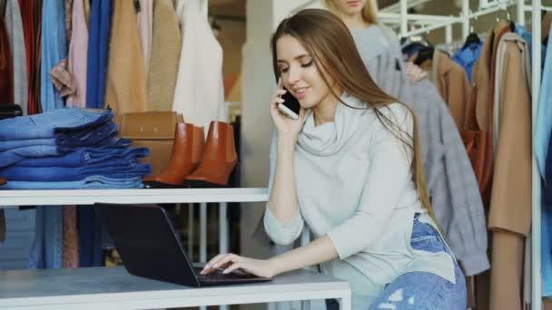 Ženské majitel butiku oblečení je mluvit na mobilním telefonu a psaní na notebooku. Její asistent se blíží ji, a ona dává příkazy v přátelsky