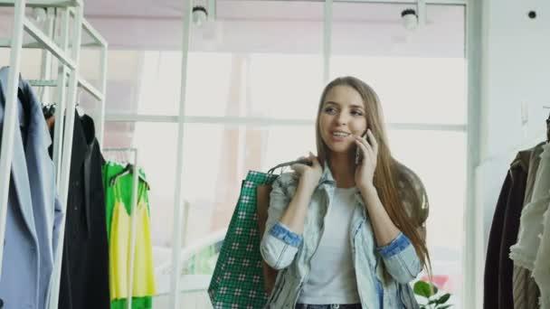 Dolly lövés a fiatal nő séta ruházat, és beszél a mozgatható telefon-val táskák a kezében. Rengeteg ruhák és cipők a háttérben.