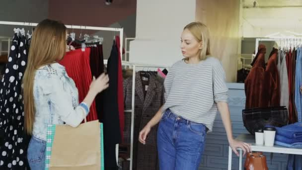 Female friends are shopping together. They are standing beside rails with womens clothes, taking pleated skirt, looking at it carefully and fitting it while chatting and smiling
