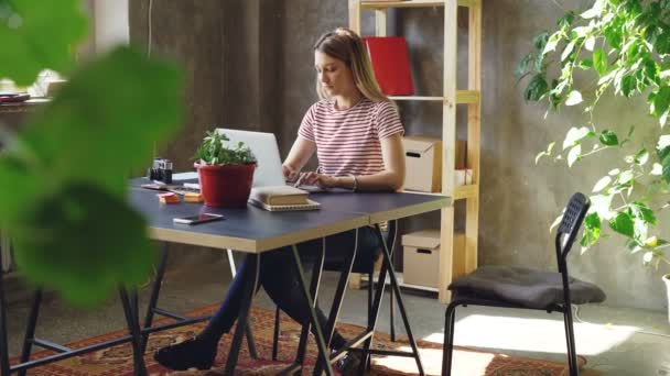 Young woman is working with laptop sitting at table in office. Her colleague is coming, women start watching screen together and laughing. Informal friendly atmosphere.