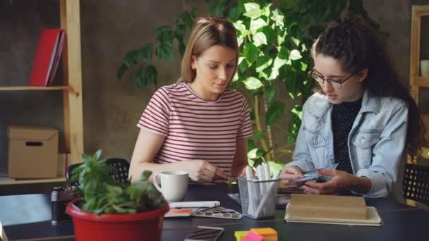Mladých kreativních návrhářů jsou pozorně prohlíží fotografie a diskutování o nich zároveň seděli spolu u stolu. Pan záběr funkčního stylu moderní loft