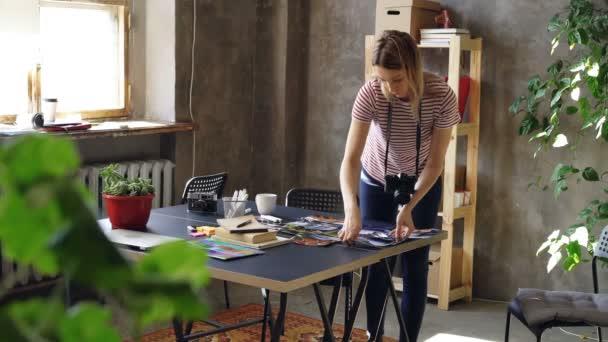 Mladá kreativní dívka dělá, ploché uspořádaní barevné fotografie, pak je Střelba s kamerou. Žena stojící nedaleko moderní stůl a nosí ležérní oblečení