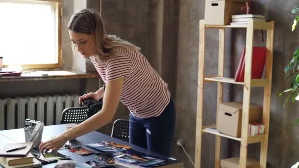 Fiatal vonzó női blogger digitális fényképezőgép segítségével lőni a színes képek utazási jelenik meg a táblázatban. Ő mozgó képek és kollázsokat, hogy.