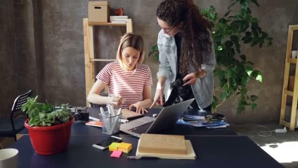 Mladí kreativní kolegové plánují design, rozvržení výkresu v poznámkovém bloku a sledováním fotografie na obrazovku fotoaparátu. Ženy jsou zaneprázdněni prací na projektu důležité