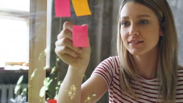 Detail hezká mladá žena s blond vlasy, barevné poznámky na skleněné desce v moderní kanceláři. Ona se při pohledu na papíry a usmívá se