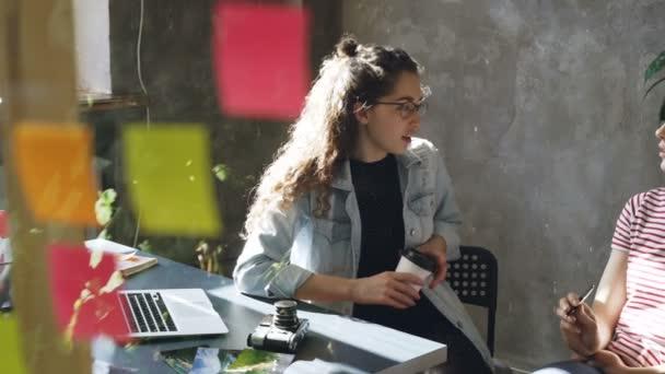 Üzletasszonyok ülő-on iskolapad együtt, és megvitatni a korszerű új projekt. Üveg előtérben színes matricával.
