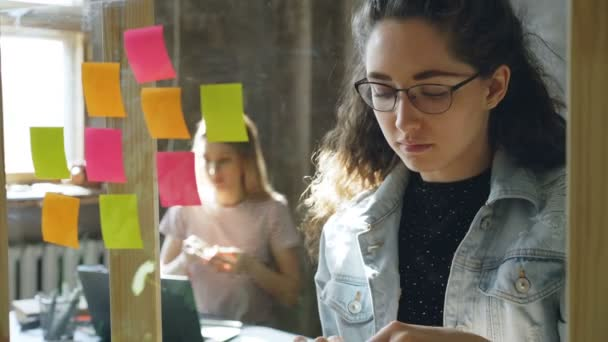 Close-up shot of attractive young businesswoman standing and sticking colourful memos on glass board. Her colleague is sitting and working in background. Creative work concept.