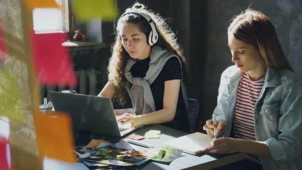 Team di creativi è lavorare insieme nellufficio della luce. Signora dai capelli scuri è ascoltare musica e lavorare con il computer portatile, e donna bionda è disegnare immagini in blocco note