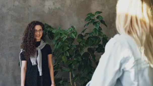 Krásná mladá dáma s dlouhými tmavými vlasy kudrnaté je pózovat s velkých zelených rostlin, zatímco fotograf je natáčení ji. Tvář dívky je opravdu emotivní, se baví