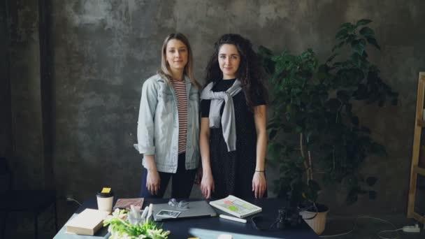 Dvě mladé ženy se spolupracovníky jsou stáli v podkroví styl úřadu, pózování a při pohledu na fotoaparát. Dívky jsou radost, úsměv a smích