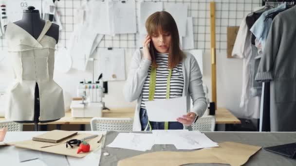Mladá atraktivní švadlena je diskuse o oděvní design na mobilním telefonu a kontrola skici při práci v jejím ateliéru mezi figurínu a kolejnicí s oblečením.